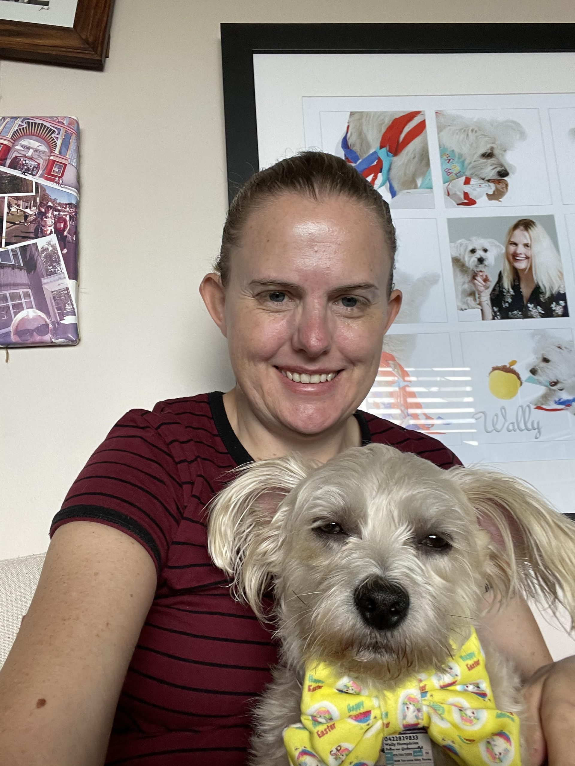 An image of Jody who has dark hair, light skin and a stripy red and black top. She's smiling and holding an adorable white dog in the foreground.